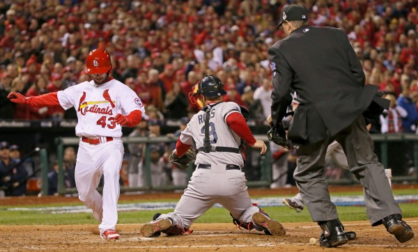 St. Louis Cardinals pinch hitter Shane Robinson touches home on a  hit by Matt Carpenter before Boston Red Sox catcher David Ross can make the tag during the seventh inning in Game 4 of the World Series on Sunday, October 27, 2013, at Busch Stadium in St. Louis Sunday night.