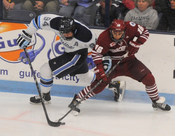 The University of Maine's Devin Shore (left) and UMass's Steven Iacobellis battle for the puck during the first period of the game in Orono Saturday night.