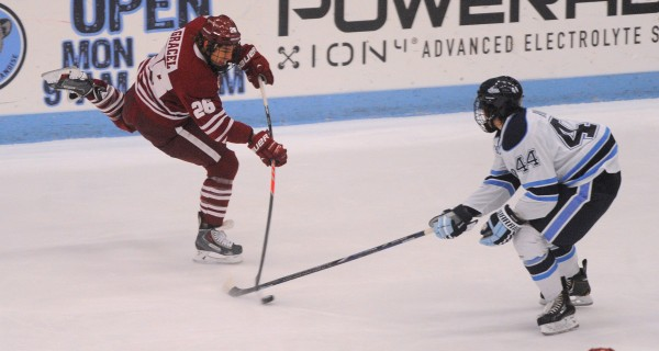 The University of Maine's Conor Riley (right) tries to block a shot by  UMass's Branden Gracel during the first period of the game in Orono Saturday.