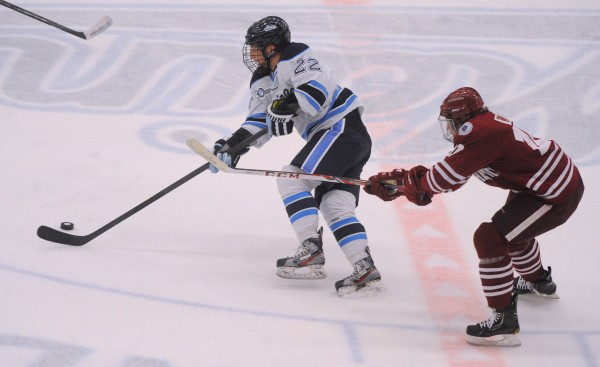 The University of Maine's Stu Higgins (left) and UMass's Shane Walsh battle for the puck during the first period of the game in Orono Saturday.
