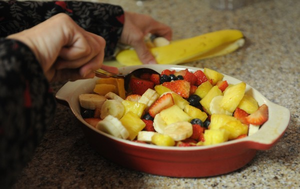 A fruit salad with sliced bananas, pineapple and blueberries and strawberries that have been marinated in vanilla balsamic vinegar.