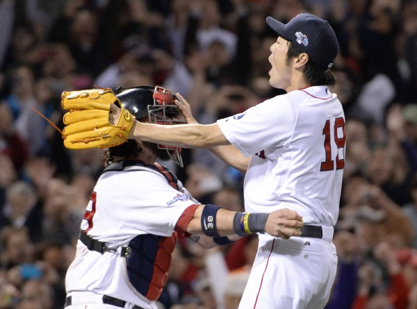 Boston Red Sox relief pitcher Koji Uehara (19) celebrates with catcher Jarrod Saltalamacchia after defeating the Detroit Tigers in game six of the American League Championship Series at Fenway Park in Boston Saturday night.