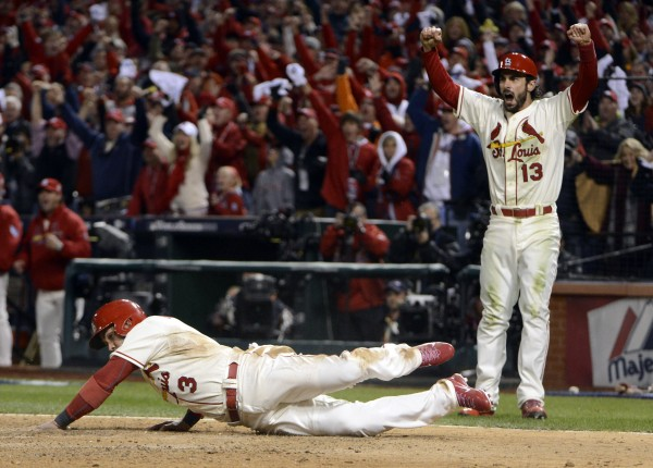 St. Louis Cardinals' Matt Carpenter (13) celebrates as teammate Carlos Beltran (3) scores a run in the seventh inning against the Boston Red Sox during game three of the World Series at Busch Stadium Saturday night.