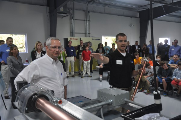 John Butera (left), Gov. Paul LePage's senior economic advisor, looks on as Nate Veilleux, a mechanical engineer at Mega Industries in Gorham, demonstrates to a room full of students how a piece of equipment designed by a summer intern from the University of Maine works.