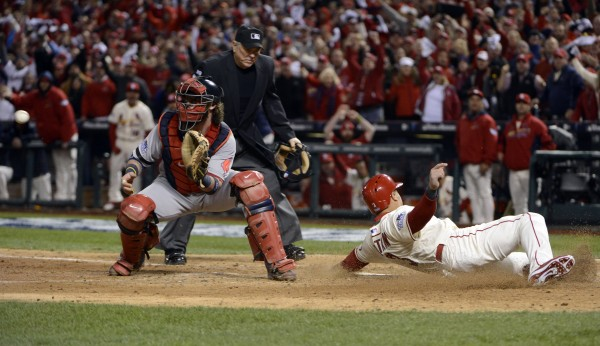 St. Louis Cardinals right fielder Carlos Beltran (3) slides past Boston Red Sox catcher Jarrod Saltalamacchia (left) to score a run in the 7th inning during game three of the World Series at Busch Stadium.