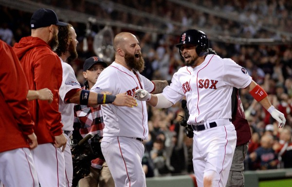 Boston Red Sox right fielder Shane Victorino (right) celebrates with teammates in the dugout after hitting a grand slam against the Detroit Tigers during the seventh inning in game six of the American League Championship Series Saturday night in Boston.