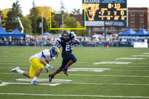 The University of Maine's Nigel Jones advances the ball against the University of Delaware's Craig Brodsky during the first quarter on Saturday afternoon at Morse Field in Orono.