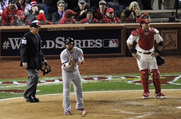 Boston Red Sox right fielder Shane Victorino (18) reacts after scoring as St. Louis Cardinals catcher Yadier Molina (4) looks on during the sixth inning of game three of the MLB baseball World Series at Busch Stadium Saturday night.
