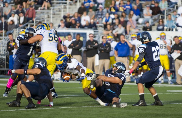 The University of Maine's Troy Eastman (right) tackles the University of Delaware's Rob Jones in the second quarter of Saturday afternoon's home game held in Orono at Morse Field.