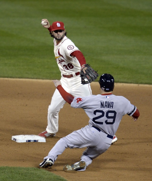 St. Louis Cardinals shortstop Pete Kozma (38) turns a double play over Boston's Daniel Nava (29) in the sixth inning during game three of thel World Series at Busch Stadium Saturday night.