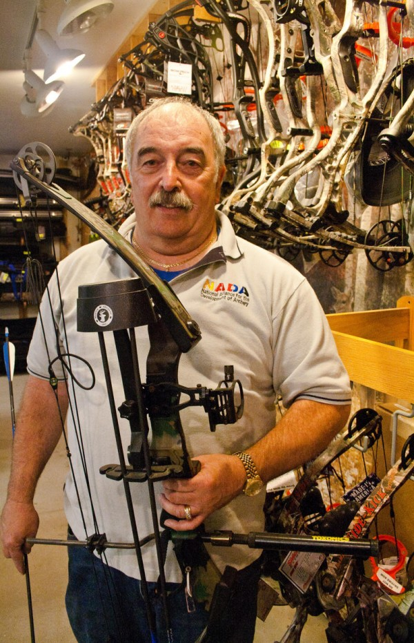 Steve Dunsmoor, owner of Lakeside Archery in North Yarmouth, stands next to his inventory of compound bows. Dunsmoor said archery has grown in popularity in recent years due to the Olympics and movies like &quotBrave&quot and &quotThe Hunger Games.&quot