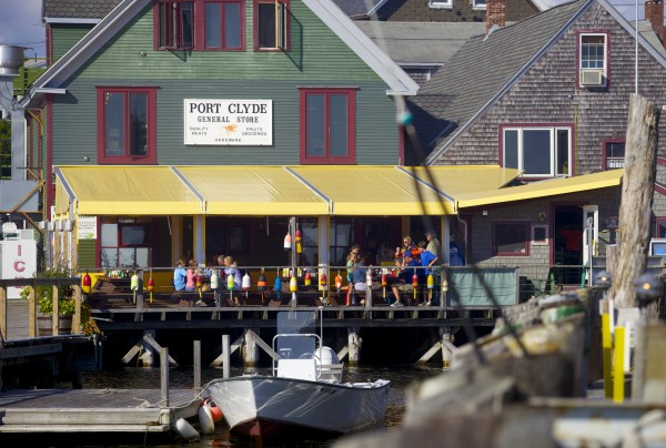 Visitors eat at on a deck next to the  Monhegan Boat Line dock in Port Clyde just days after the August 11 crash that killed a child, injured a family and damaged several parked cars.
