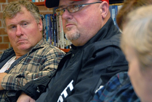 Rob Farrington (left), chairman of the Medway Board of Selectmen, peers across Millinocket Town Councilor John Raymond as he listens to Millinocket Town Manager Peggy Daigle at a meeting at the East Millinocket library on Monday, Oct. 15, 2013.