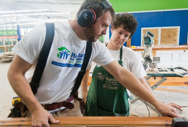 Employees Andrew Smith and Alexa Plotkin prepare to rip moulding on a table saw in the new Habitat for Humanity of Greater Portland ReStore on Warren Avenue in Portland. The new space is much larger than a previous location and is expected to generate more than twice the revenue for the nonprofit organization. A reopening ceremony is planned for Saturday, Oct. 19.