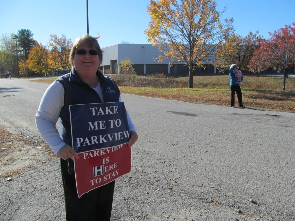Valerie Caron of Harpswell waves signs outside a hearing Wednesday, Oct. 24, 2012, where the Maine Department of Health and Human Services was gathering comments regarding a proposal for a merger between Central Maine Healthcare and Parkview Adventist Medical Center in Brunswick.