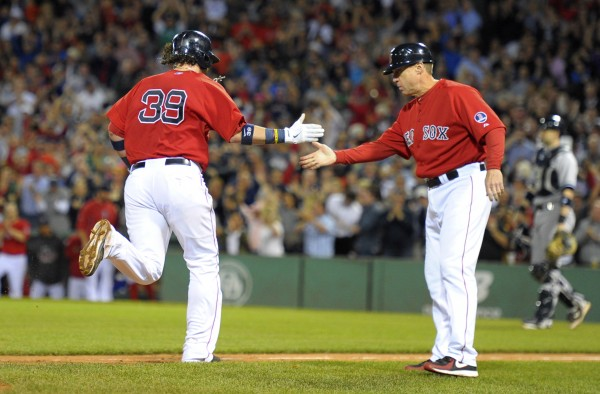 Boston Red Sox third base coach Brian Butterfield (13) greets Jarrod Saltalamacchia after he hit a grand slam against the New York Yankees during a game on Sept. 13 in Boston. Butterfield, an Orono native, is helping the team prepare for the World Series, which opens Wednesday night at Fenway Park against the St. Louis Cardinals.