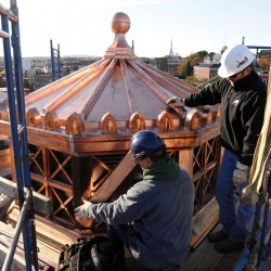 Coppersmith David Hazelton, left,  assembles copper trim work on the Bangor Public Library cupola as Roof Systems of Maine vice president Lee Corro watches on Friday morning.