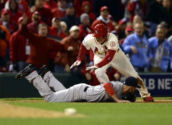 St. Louis Cardinals designated hitter Allen Craig (21) is tripped by Boston Red Sox third baseman Will Middlebrooks (16) during the ninth inning and would score on an obstruction call to win game three of the World Series at Busch Stadium Saturday night. The Cardinals won 5-4.