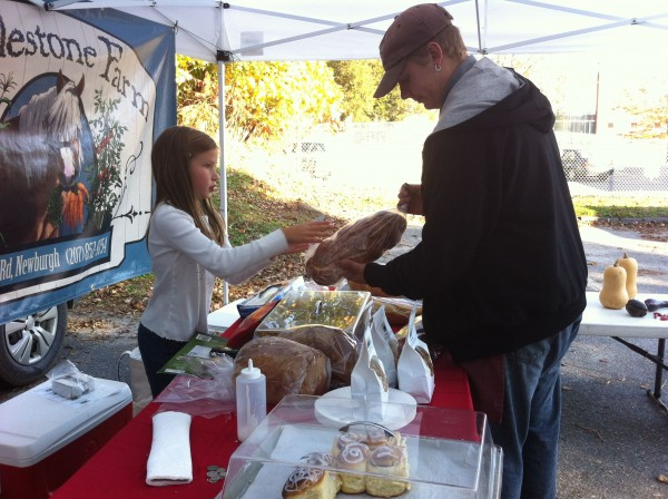 Zoe Sikkel, 7, sells bread to Andy Hall at the Bucksport Bay Farmers' Market. Sikkel helps Jenny Johnson sell baked goods here almost every week.