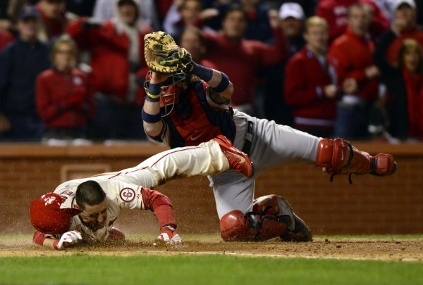 St. Louis Cardinals designated hitter Allen Craig (21) scores the winning run on an obstruction call even though Boston Red Sox catcher Jarrod Saltalamacchia (39) gets the tag on him during the ninth inning of game three of the World Series at Busch Stadium Saturday night. The Cardinals won 5-4.