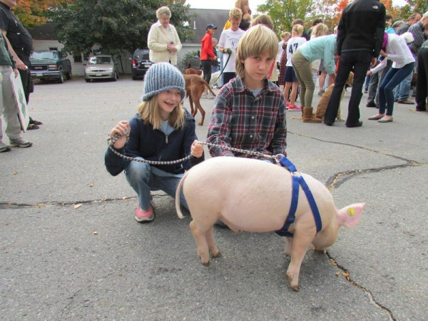 Katie McGrath Holmquist, 10, of Gray, and her brother Caleb, 12, played with her pig, Henry, at Saturday's blessing of the animals in Yarmouth.