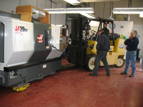 In this 2011 file photo, Dean Duplessis (far right), lead instructor of Northern Maine Community College's precision metals manufacturing program, looks on as a new state-of-the-art Haas automation lathe was delivered and installed in the college's CNC lab.
