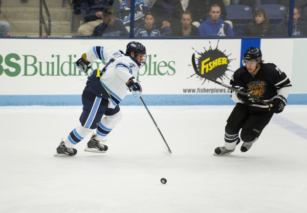 The University of Maine's Jake Rutt (left) tries to take possession of the puck from Dalhousie University's Chris Ivanko during the second period Sunday at the Alfond Arena in Orono.