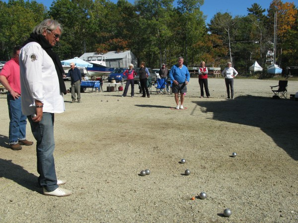 French petanque player Marco Foyot, one of the best players in the world, watches as Mainers try their hand at the game Sunday during a tournament with the Maine Boules Club.