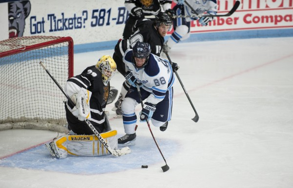 The University of Maine's Brian Morgan puts pressure on Dalhousie goalie Bobby Nadeau of Dalhousie University during the first period Sunday at Alfond Arena in Orono.