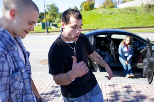 Garrett Brown (left) listens to Paul Fazzi rap a song that he wrote while performing for him in Bangor. Fazzi says he uses his life experiences and struggle with addiction for musical inspiration.