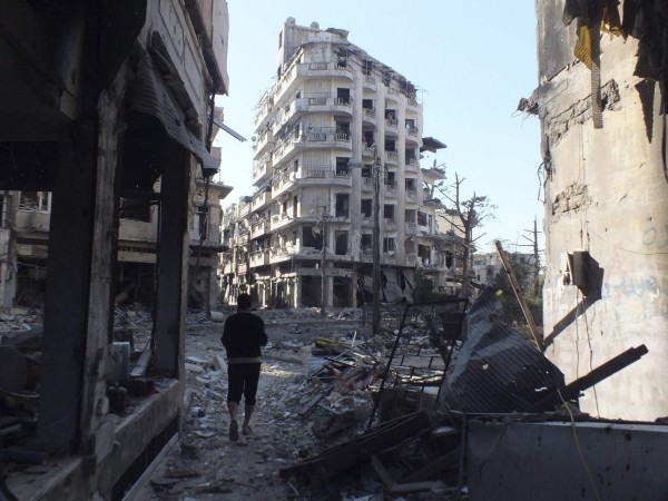 A Syrian resident walks past rubble and damaged buildings in a sieged area of Homs on Saturday, Oct. 12.
