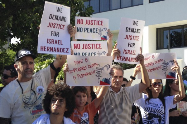 Demonstrators march through Miami Beach October 6, 2013 during a protest over the death of a graffiti artist who died in police custody August 6.  The protesters alleged that Officer Jorge Mercado used excessive force when he used a Taser on Israel Hernandez-Llach, 18, during an arrest attempt in August.