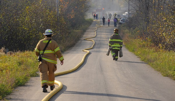 Firefighters walk toward a house fire on Sawyer Road in Levant.
