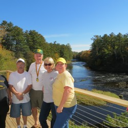 Several members of the Island Falls team that has worked on reviving the town's economy stands on the back deck of the new River Cafe. From left are Libby Moulton, Skip Lewin, Pete Connelly, Cheryl Connelly and Tabby York.