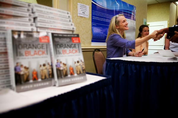 Piper Kerman, author of &quotOrange is the New Black,&quot signs her book in Portland Tuesday at a Tuesday conference about women in prison. The book has been adapted into an acclaimed show on Netflix.