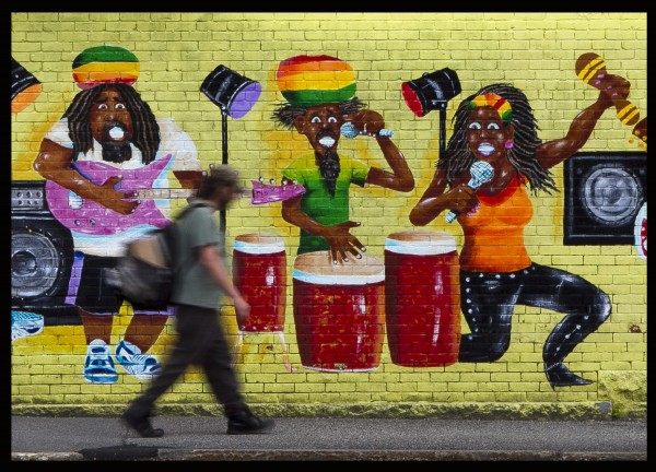 Musicians wearing Rastafarian headwear appear to take notice of a pedestrian on Cedar Street outside the Lewiston Pawn Shop.