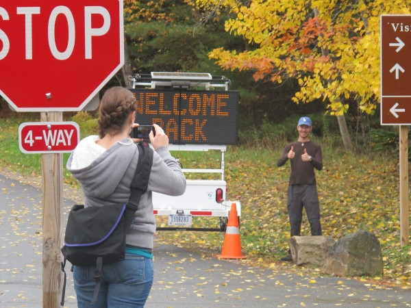 Courtney Ames takes a photograph of Mike McCann by an electronic sign at the Acadia National Park Visitors Center in Bar Harbor. The park reopened Thursday.