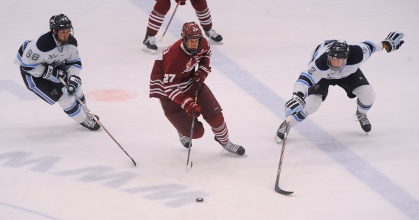 UMass's Adam Phillips (center) skates with the puck between the University of Maine's Dan Renouff (right) and Brian Morgan during the first period of the game in Orono Saturday night.
