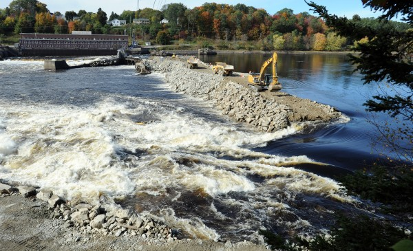 On Oct. 10, as part of the Penobscot River Restoration Project, the upper coffer dam is being breached.  Sargent Corporation used a large excavator to start removing the 16,000 cubic yards of rock.