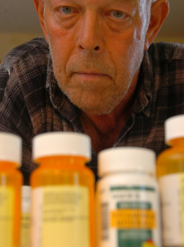 Jim Barrows, who has cancer, is shown with his medications at his home in Hampden. After noticing that some of his neighbors also have cancer, he hopes to enlist the state's help in determining whether these cancers are connected to the area of town in which they live.