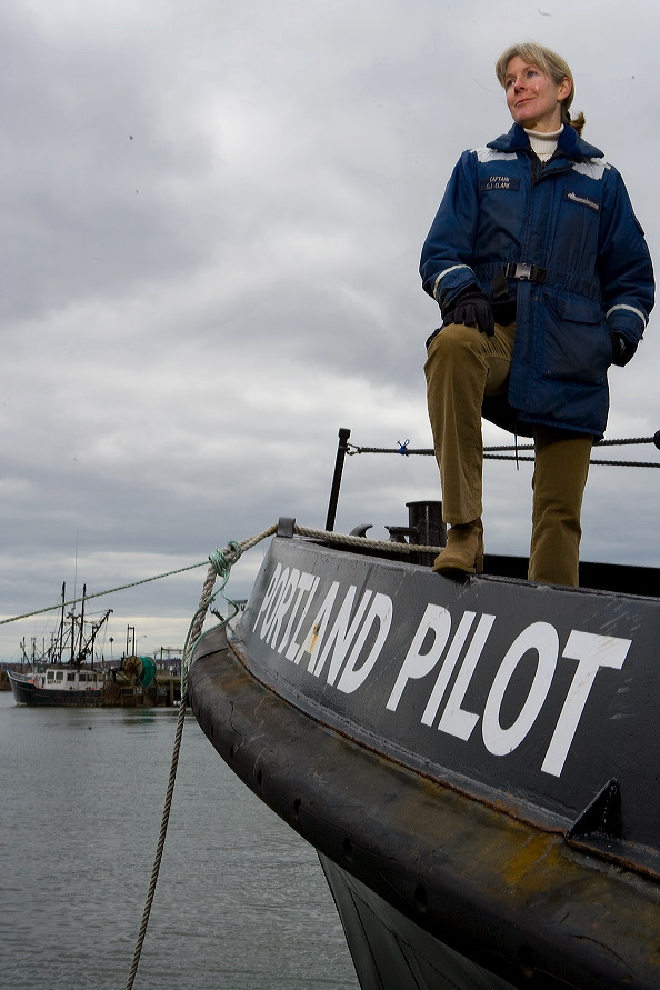 Susan Clark stands at the stern of a Portland Pilots ship before she died. A Maine Maritime Academy training vessel recently was renamed in her honor.