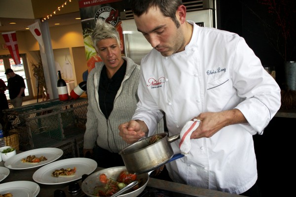 Winner of the Harvest on the Harbor lobster cooking contest Chef Chris Long, of Natalie's at the Camden Harbour Inn, prepares butter poached lobster with grilled local mushrooms, corn, parsnip ragout and thyme butter while host Michele Ragussis looks on Thursday in Portland.