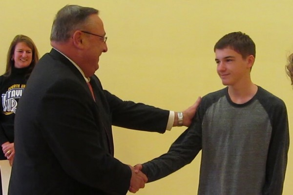 Gov. Paul LePage shakes the hand of 14-year-old Gabriel Brady, whose mother was killed in a domestic violence altercation in January 2008. The exchange came during a kick-off event for the fifth annual Taylor Tip Off Basketball Tournament, the proceeds from which benefit the families of domestic violence victims.