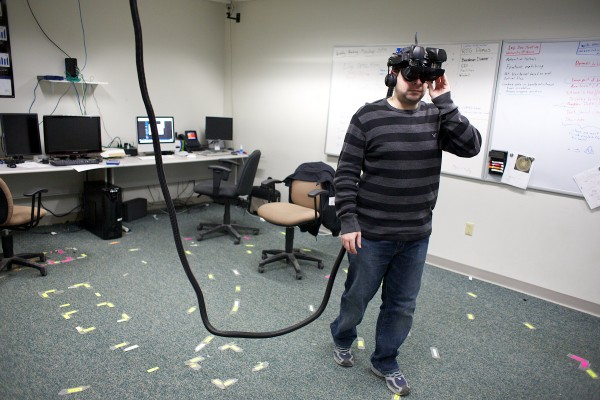 University of Maine third-year PhD candidate Chris Bennett walks around with a virtual reality headset at the Virtual Environment and Multimodal Interaction Laboratory at the Orono campus in February. Students have been working on virtual reality programs to help the visually impaired, firefighters in smoke-filled rooms,  and others &quotsee&quot buildings through augmented reality.