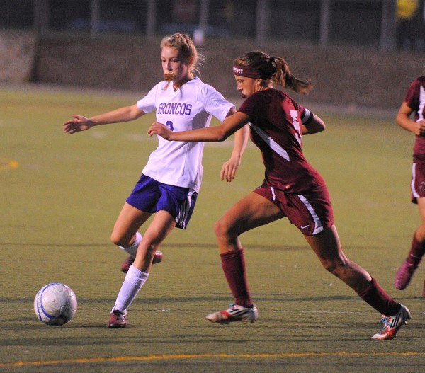Hampden Academy's Abby Lord (left) and Edward Little's Sarah Hammond battle for the ball during the first half of the game in Hampden on Friday evening.