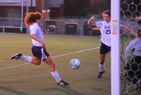 Hampden Academy's Naomi Shearer (left) charges ahead to score the second goal in the first half against Edward Little in Hampden on Friday evening.  At center is Karry Quigley providing coverage on the play.