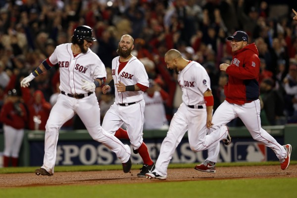 Boston Red Sox first baseman Mike Napoli (12) and right fielder Shane Victorino (18) chase catcher Jarrod Saltalamacchia (39) after defeating the Detroit Tigers 6-5 in game two of the American League Championship Series at Fenway Park in Boston Sunday night. The Boston Red Sox won 6-5.
