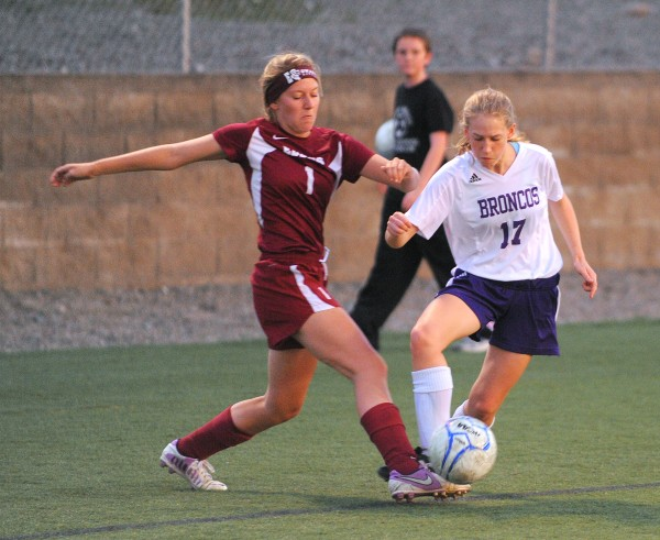 Edward Little's Emily Schario (left) and Hampden Academy's Taemer Shearer battle for the ball during the first half of the game in Hampden on Friday evening.