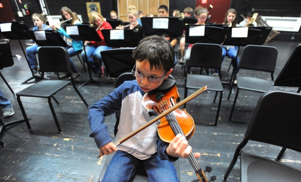 Bangor Symphony Youth Orchestras' second violinist Colin Aponte goes over a piece during a break while rehearsing at the Bangor High School