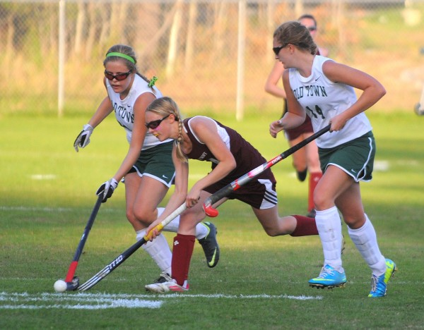 Foxcroft Academy's Madison Fadley (center) drives between Old Town's Sarah Plunkett (left) and  Lizzy Colanino during the second half of the game in Old Town on Tuesday afternoon.